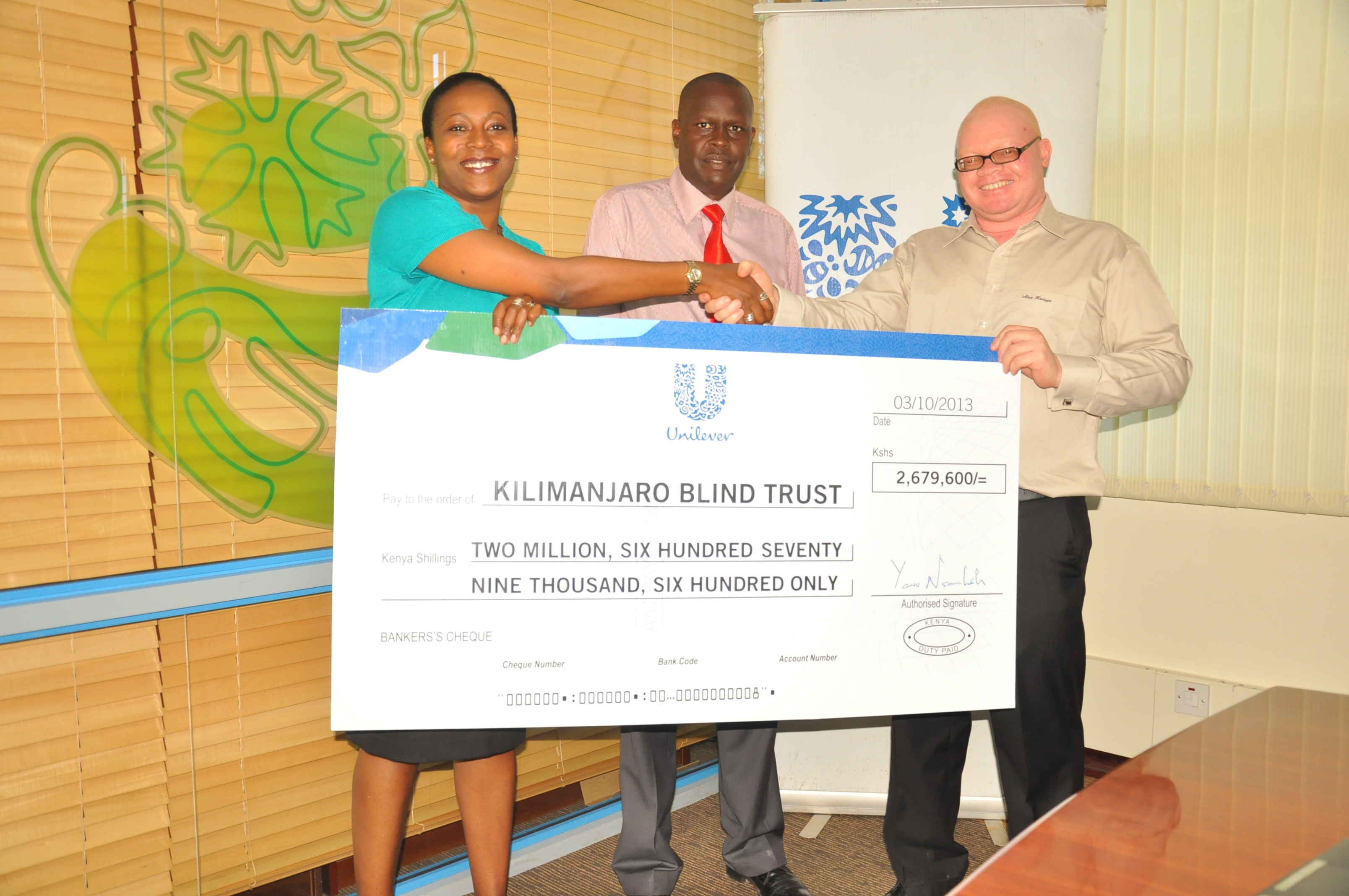 Susan handing KBT grant to Juma and Alex